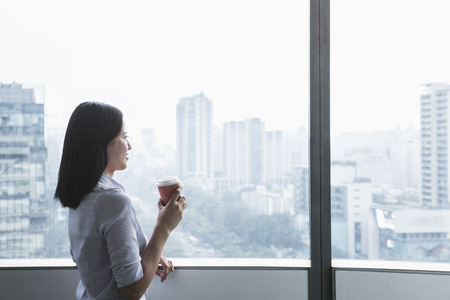 window view: Smiling young businesswoman holding a coffee cup and looking out the window a the cityscape in Beijing, China