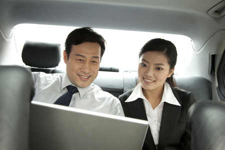 two persons only: business people working with laptop in the car Stock Photo