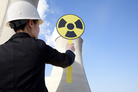 cooling towers: Engineer in front of cooling towers with sign