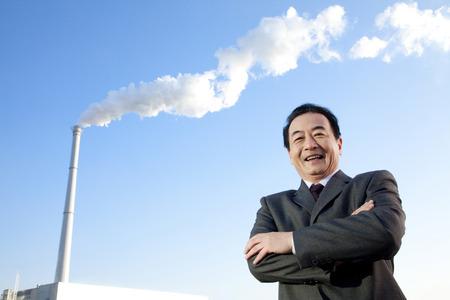 smokestack: Businessman in Front of Smokestack Stock Photo
