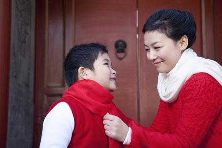 niños vistiendose: Momento blando entre madre e hijo