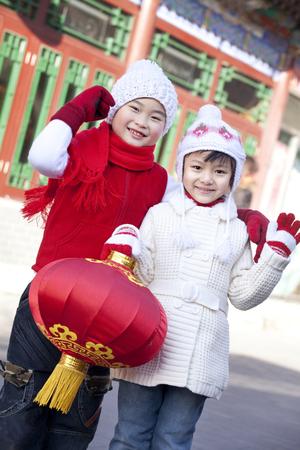 niños vistiendose: Niños que sostienen la linterna roja