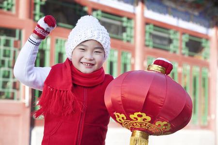 niños vistiendose: El muchacho joven que sostiene la linterna roja