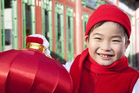 one boy only: Boy holding red lantern in Courtyard