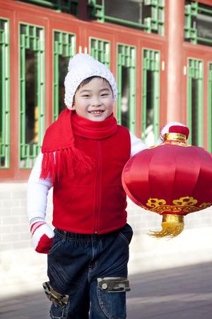 niños vistiendose: Muchacho que sostiene la linterna roja en el patio