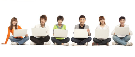Six young people sitting in a row using their laptop computers