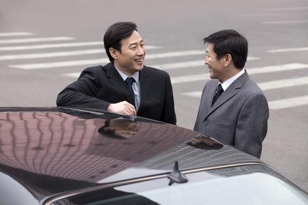 40 44 years: Two businessmen working outside in street