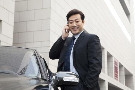 Businessman talking on phone outdoors near a car