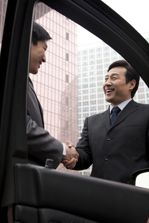 40 44 years: Two businessmen working outside near a car