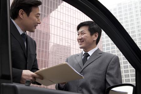 Two businessmen working outside near car