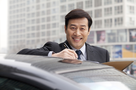 40 44 years: Businessman smiling, working outdoors on a car