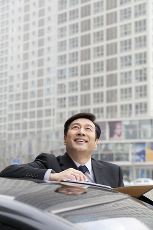 Businessman smiling, working outdoors on a car