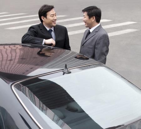 40 44 years: businessmen talking beside a car