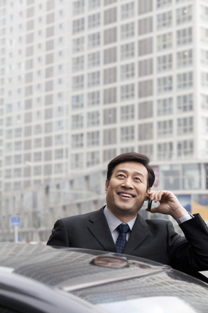 40 44 years: Businessman talking on phone outdoors on car