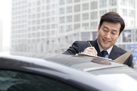 40 44 years: Businessman working on a car
