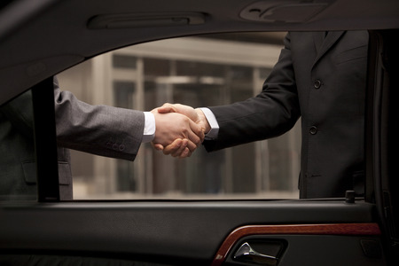 asian professional: Two businessmen shaking hand through car window outside Stock Photo