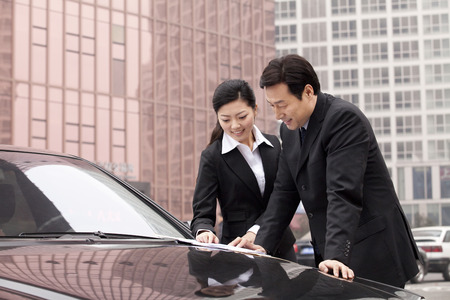 40 44 years: Businesspeople working outdoors on a car