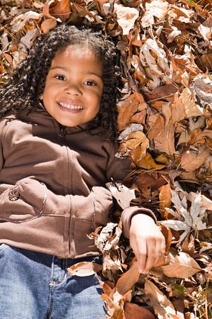 cabello negro: Chica mentir en hojas Foto de archivo