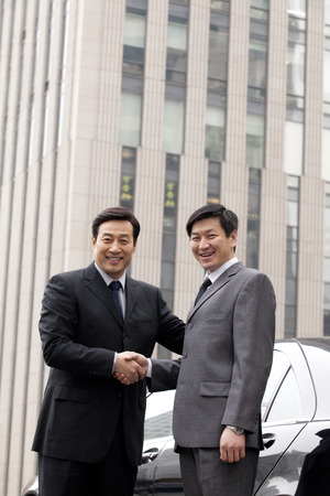 40 44 years: Two businessmen shaking hands outdoor