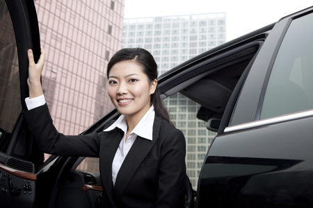 exiting: Businesswoman exiting a car Stock Photo
