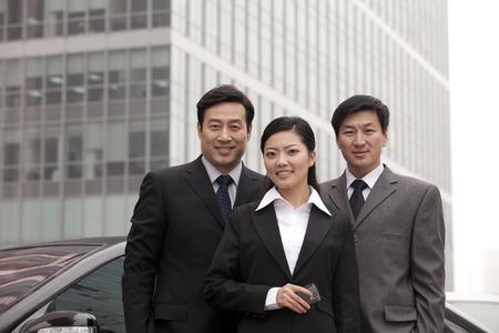 40 44 years: Three businesspeople outdoors near car Stock Photo
