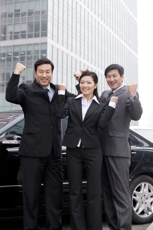 40 44 years: Three businesspeople outdoors cheering near car