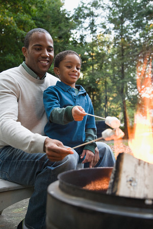 family with two children: Father and son toasting marshmallows Stock Photo