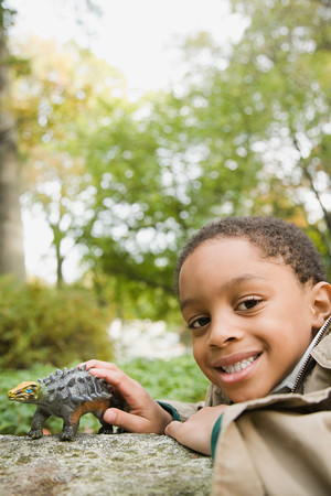 only one boy: Boy with toy dinosaur Stock Photo