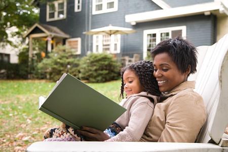 black girl: Mutter und Tochter mit Buch Lizenzfreie Bilder