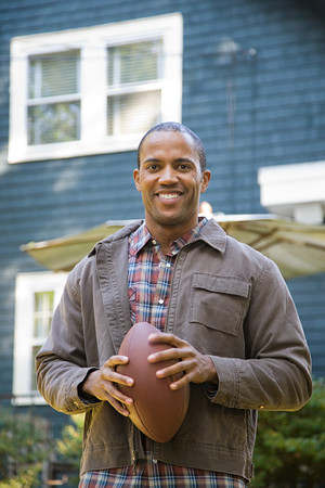 new home: Man holding an American football Stock Photo