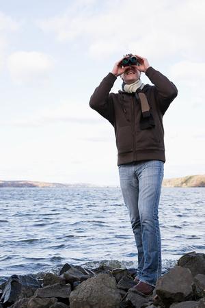 mid distance: the man using binoculars
