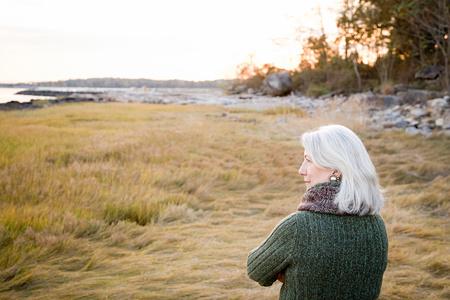 personas de pie: Mujer de pie sobre la hierba cerca de la costa