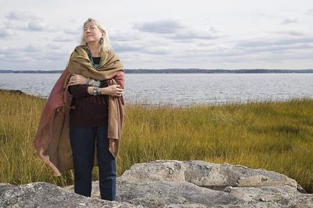 Senior woman standing near a lake