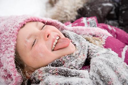 sticking out tongue: Chica en la nieve sacar la lengua Foto de archivo