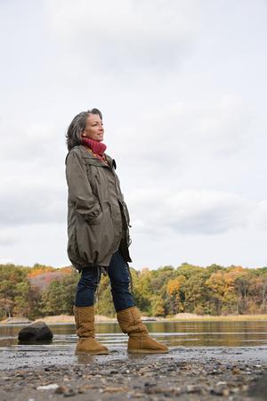 greying: Mature woman standing near a lake