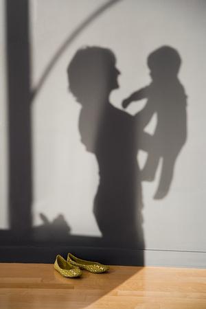 赤ん坊を抱える女性の影
