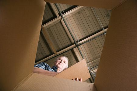 empty warehouse: Man looking in cardboard box Stock Photo