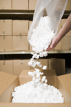cardboard only: Person putting packing peanuts in box