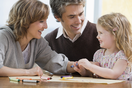 child smiling: Parents helping their daughter draw