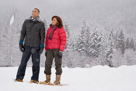 british ethnicity: Portrait of a mature couple wearing snowshoes Stock Photo
