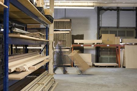 man pushing: Man pushing boxes in warehouse