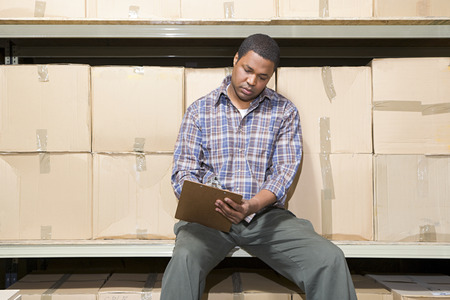 taking inventory: Man in warehouse Stock Photo