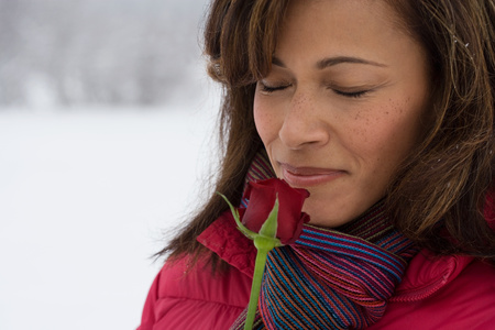 british ethnicity: A mature woman smelling a rose
