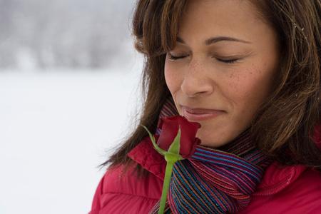 mujer con rosas: Una mujer madura que huele una rosa