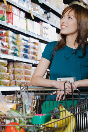 woman looking: woman pushing a shopping trolley