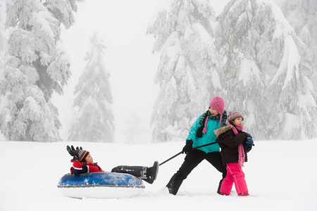 family with three children: Boy on inflatable toboggan Stock Photo