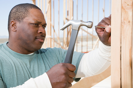 A man hitting a nail with a hammer Stock Photo