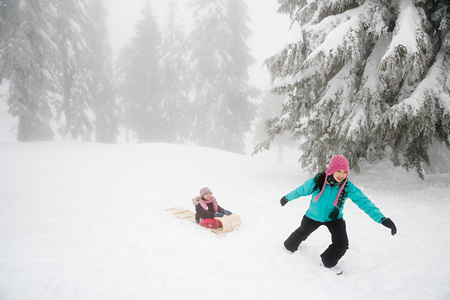 winter weather: Mother and daughter with toboggan