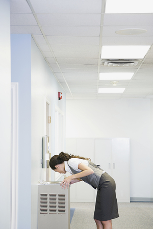 office attire: Office worker at water fountain Stock Photo