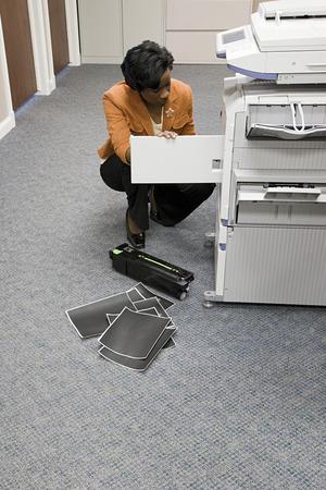 fotocopiadora: Empleado de oficina mirando fotocopiadora